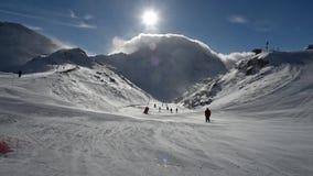 Skiërs op piste die bergaf in sterke winden gaan stock footage