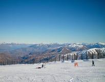 Skiërs tegen een achtergrond van bergen Stock Foto