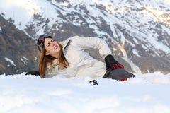 Skiërvrouw in de sneeuw wordt gekwetst die stock fotografie