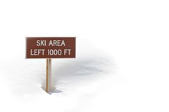 Ski area sign in snow. Ski area sign in the snow, left 1000 feet. full frame, blown highlights to obtain white background Royalty Free Stock Images
