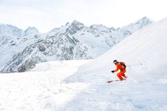 Ski athlete in a fresh snow powder rushes down the snow slope Royalty Free Stock Photography