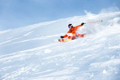 Ski athlete in a fresh snow powder rushes down the snow slope Stock Image