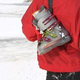 Ski boot. Close up of ski boot hung over shoulder of shoulder of male teenager royalty free stock photos