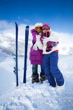 Ski buddies. Two cute kids girls hugging with skis and mountain on background Stock Photography
