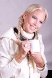 Ski Bunny with mug. Passive posed image of attractive blond girl dressed in all white winter clothes with jewelry and ski goggles holding blank white cup Royalty Free Stock Photography