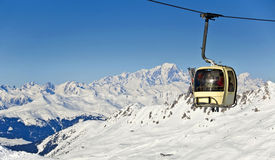 Ski cable car, snowy Alps mountains and the Mont-Blanc Royalty Free Stock Image