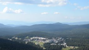 Ski Center Kopaonik. Panning shot from the top of Kopaonik mountain, to the ski resort during summer. Camera stop moving briefly and after 6 seconds of pause stock footage