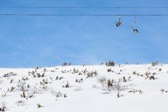 Ski chair lift against blue sky. Ski chair lift with two double seats, against blue sky, above snowy field Royalty Free Stock Photography