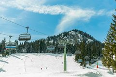 Ski chair lift in the Alps against the blue sky, forest and mountains royalty free stock photography