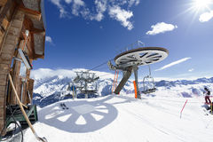 Ski chair-lift arrival in alpine mountain. With sun, France Stock Image