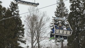 Ski chair lift with skiers stock footage