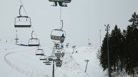 Ski chair lift with skiers stock video footage