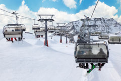 Ski chair-lift with skiers in mountains Stock Image