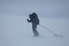 Ski, der Mann mit Schlitten im schlechten Wetter bereist Stockfotografie