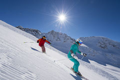 Ski downhill with sun in the background. Skiing by sunny weather - in the background the sun Stock Photos