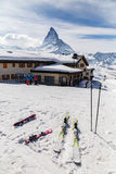 Ski equipment place on snow ground. Ski equipment place on snow ground with the background of restaurant and Matterhorn stock photography