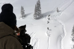 Ski film. A ski film photographer records an extreme skier flipping and spinning Stock Photography