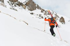 The ski freerider climbs the slope into deep snow powder with the equipment on the back fixed on the backpack. The concept of winter extreme sports Stock Image