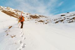 The ski freerider climbs the slope into deep snow powder with the equipment on the back fixed on the backpack. The concept of winter extreme sports Royalty Free Stock Images