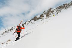 The ski freerider climbs the slope into deep snow powder with the equipment on the back fixed on the backpack. The concept of winter extreme sports Stock Photos