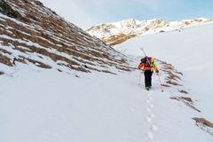 The ski freerider climbs the slope into deep snow powder with the equipment on the back fixed on the backpack. The concept of winter extreme sports Stock Images