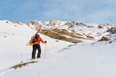 The ski freerider climbs the slope into deep snow powder with the equipment on the back fixed on the backpack. The concept of winter extreme sports Stock Photography