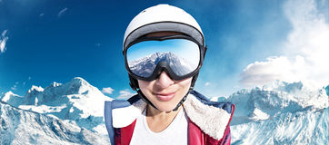 Ski girl. In front of the snowy mountains stock photography