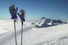 Ski gloves on poles on the background of southern slope Aibga Ridge of Western Caucasus at Rosa Khutor Alpine Resort Stock Photo