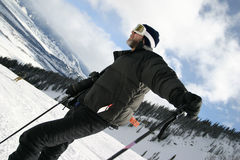 Ski Guy Camera. A middle aged man in a black ski outfit with a camera hanging from his neck, pauses to look over the beautiful winter ski scene. He is wearing Stock Photo