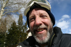 Ski Guy Happy. A middle-aged man with beard and mustache has a great smile and is ready to hit the slopes! He is wearing ski goggles on top of his head and a Royalty Free Stock Image