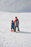 Ski instructor with children on ski lift Royalty Free Stock Image