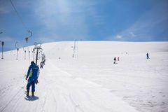 Ski instructor climbs with the ski lift. Rapino, Italy - April 01, 2017: Ski instructor climbs with the ski lift on the ski slopes of Mammarosa, Majella in Royalty Free Stock Photo