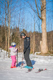 Ski instructor and little girl Stock Images