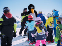 Ski instructor in penguin suit studies young skiers. Ski resort in Alps, Austria, Zams on 22 Feb 2015. Skiing, winter season, moun Stock Image