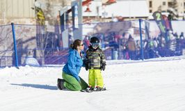 Ski Instructor Teaching a 3-Year Old Toddler Boy at a Mountain Resort royalty free stock photo