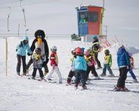 Ski instructors study young skiers in ski school. Ski resort in Royalty Free Stock Images