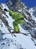 Ski jump. Skier in green performing a high jump with crossed skis Stock Photos