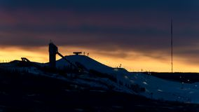 Ski jump and chair lift with orange sunset time lapse stock footage