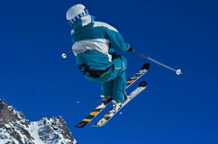 Ski Jump. Free style skier performs a high jump against a clear blue sky Stock Image