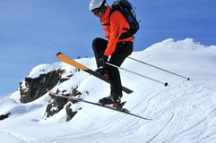 Ski jumper. Man in red and black performing a high jump. He has specially adapted bindings for ski mountaineering. He is touching his right ski with his left Stock Photography