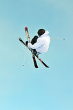 Ski jumper with crossed skis. A freeride skier jumping with crossed skis stock photo