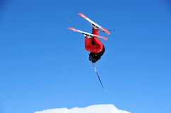 Ski jumper upside down. A ski jumper performing a complete rotation actually upside down in this image royalty free stock images