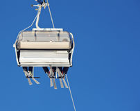 Ski lift. Chair lift with skiers at ski resort against blue sky Stock Image
