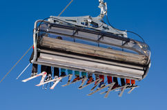 Ski lift. A ski lift with eight skiers before blue sky Stock Image