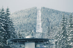 Ski lift. Wheel with mountain and  moving sportsmans; focus on foreground wheel and forest Royalty Free Stock Photo