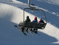 Ski lift. Three ski tourists in a air lift on their way to the top Stock Photography