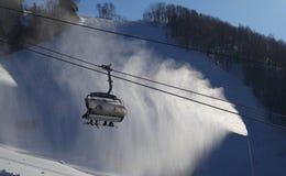 Ski lift against automized artificial snow. Ski lift gondola against automized artificial snow Stock Images