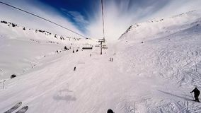 A Ski lift ascending a mountain and passing over a ski run, stock video footage
