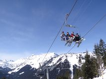 Ski lift carries holiday skiers up the mountain Royalty Free Stock Images