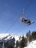 Ski lift carries holiday skiers up the mountain Royalty Free Stock Photo